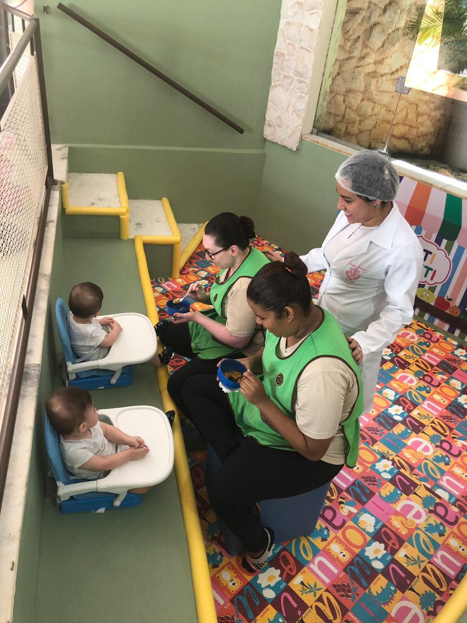 A imagem mostra duas cuidadoras dando de comer para dois bebes gêmeos, sentados em cadeirinhas especiais, no espaço tutti-frutti da Escola, enquanto a Nutricionista observa.