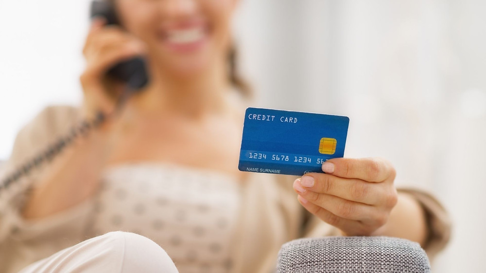 Woman on the phone while holding credit card.
