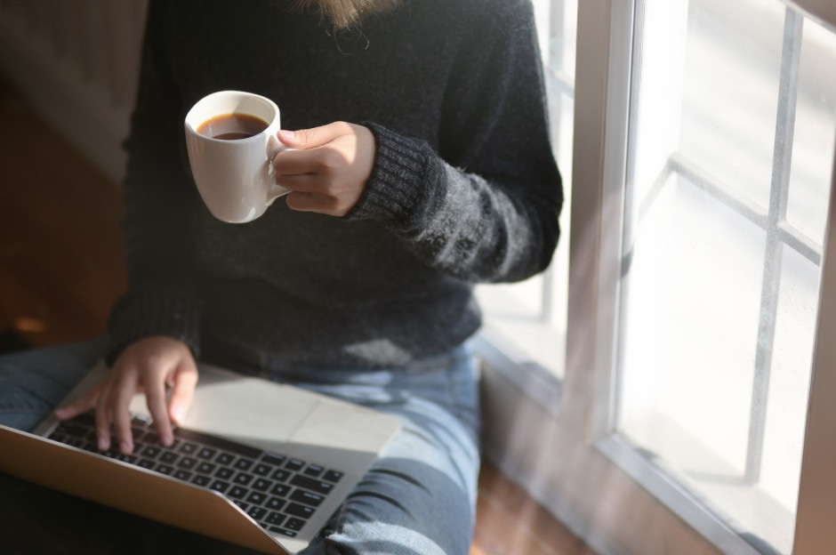 person sipping coffee while on computer