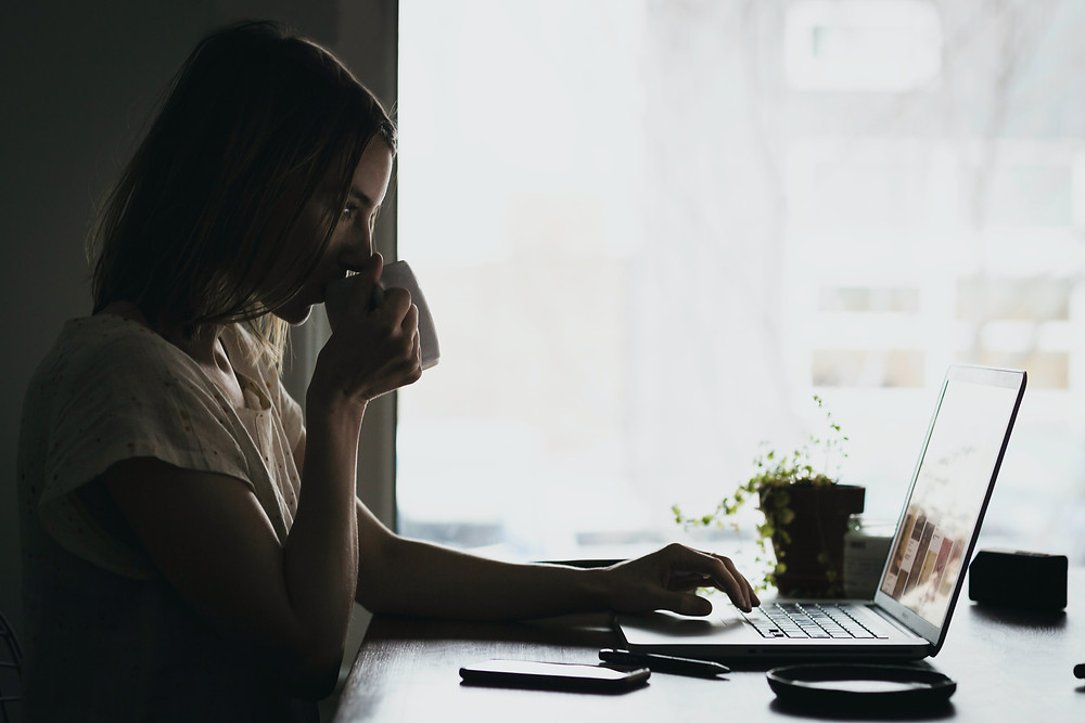 Woman drinking coffee while blogging