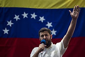 David Smolansky holds a microphone in front of a flag with his arm raised in the air