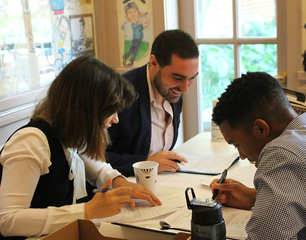 Three students laugh as they prepare for a negotiation simulation