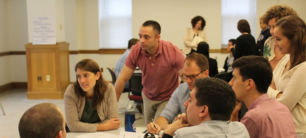 Graduate students strategize together at a table before a negotiation simulation