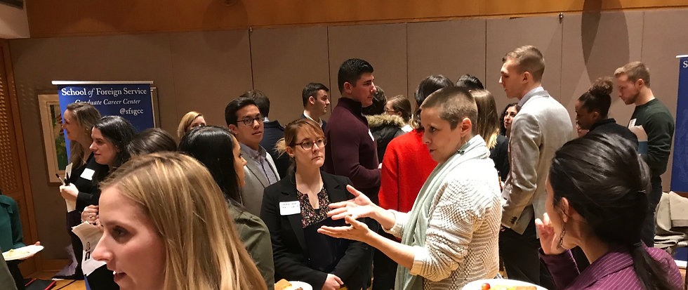 Students speak with practitioners at the networking reception