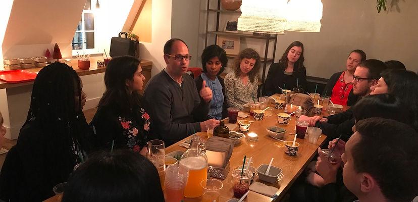 Students at a dinner table listen to Josh Wilkenfeld speak