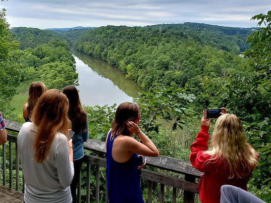 Undergraduates look onto a river and lush greenery in Radford, VA