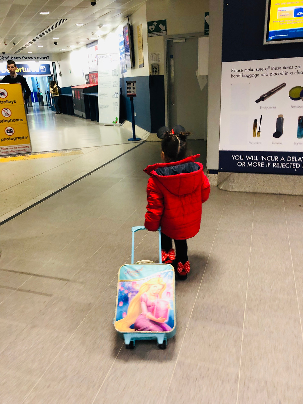 4 year old pulls a Rapunzel suitcase through airport departures