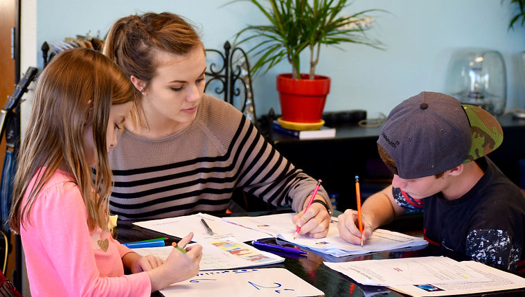two kids working with a tutor