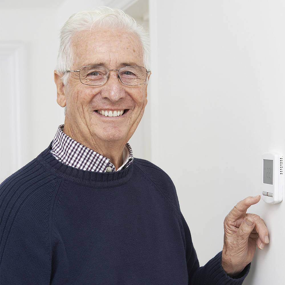 Man smiles as he sets thermostat for winter savings
