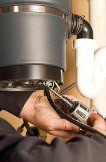 BODEK INC. technician repairs garbage disposal on kitchen sink