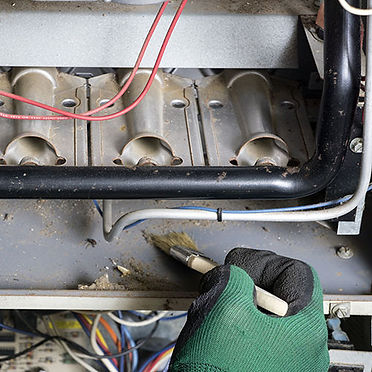 BODEK INC. technician cleans air conditioner while providing service and maintenance