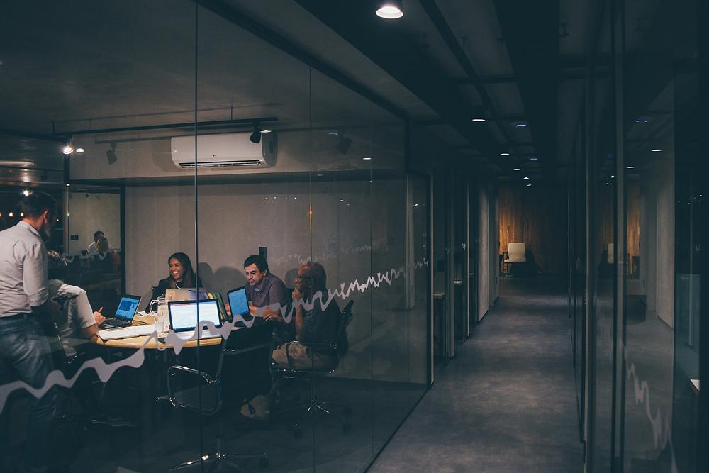 Ihmisiä neuvotteluhuoneessa tietokoneruutujen ääressä.