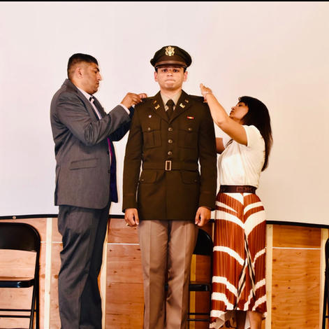 Lt Nikhil Patel being pinned by parents Bharti and Vipul Patel.