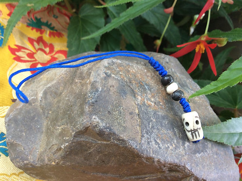 Breloque of Miniature Human skull in bone on blue string
