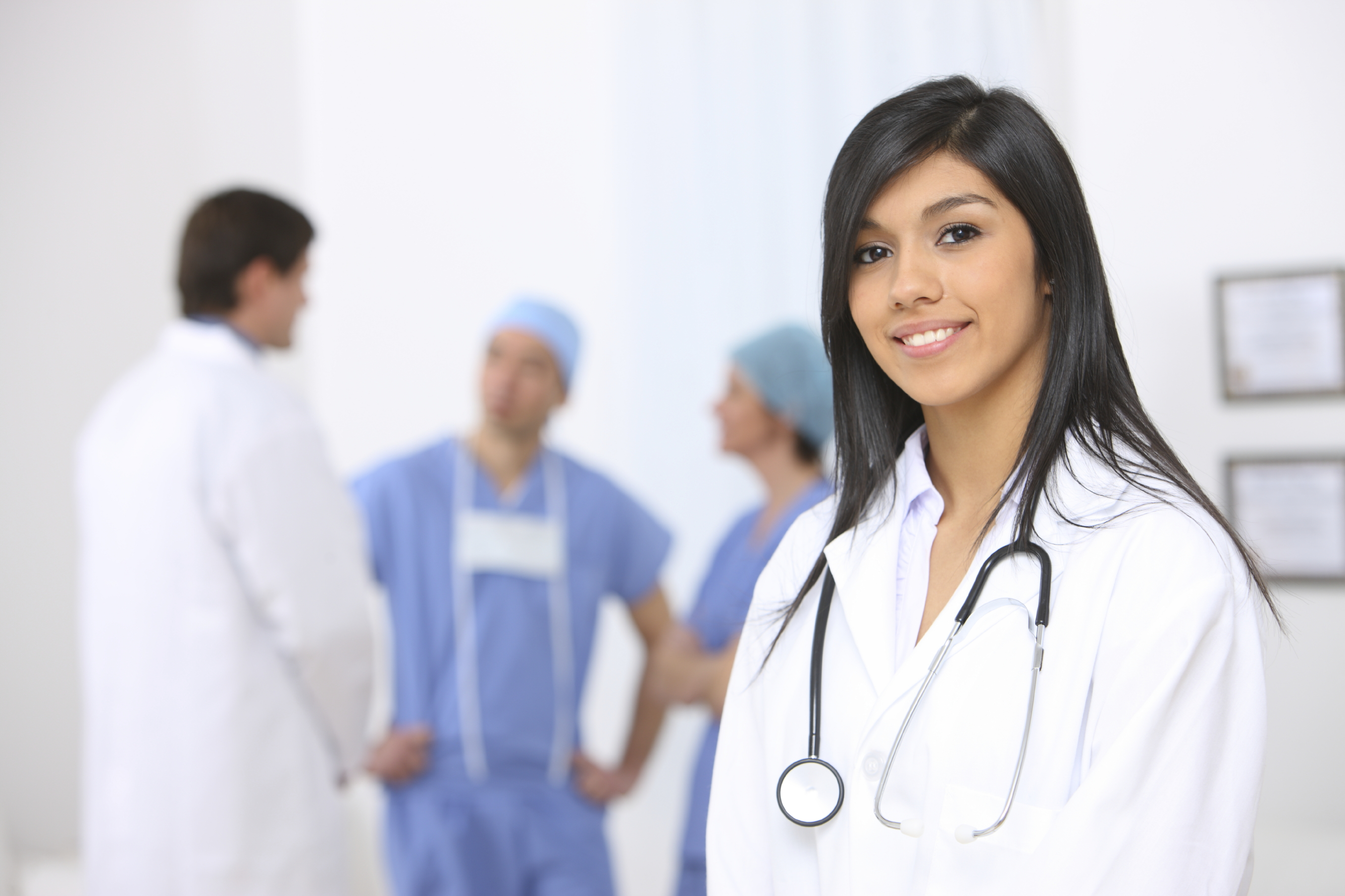 smiling_medical_doctor_with_stethoscope_on_the_hospitals_background_1350367266