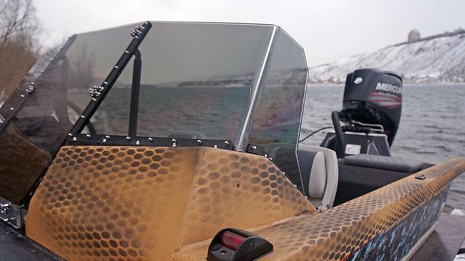 Ветровое стекло выполнено из тонированного акрила толщиной 10 мм высота стекла и отсутствие рамки не мешают обзору и достаточно защищают от ветра и дождя. При желании установки ходового тента и стеклоочистителя есть возможность изготовления ветрового стекла из триплекса.   В центре консоли имеется дверка и удобные ступеньки, позволяющие беспрепятственно попадать на нос лодки. Дверца выполнена из прозрачного акрила, что увеличивает обзор.