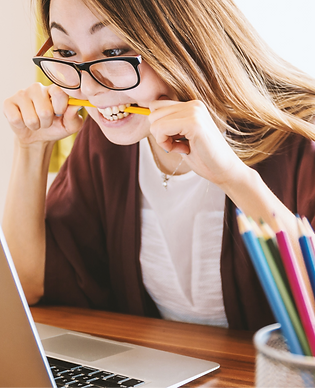 Stressed woman biting pencil while staring at computer screen_edited.png