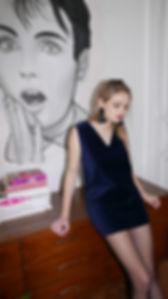 Girl wearing velvet dress leaning on a furniture
