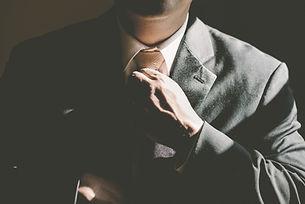 スーツとネクタイを持つ男
