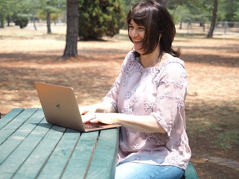 Emma on laptop park and windy.jpg