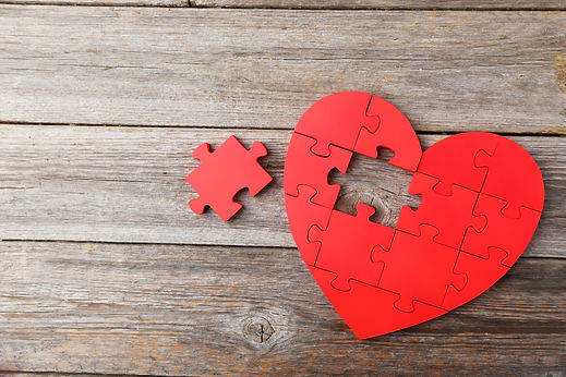 Red puzzle heart on grey wooden backgrou