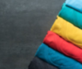 close-up-of-rolled-colorful-clothes-on-b