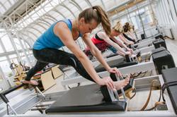 women stretching on pilates equipment