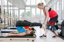 Lizzie Qualie helping clients during a cotswolds classical pilates class