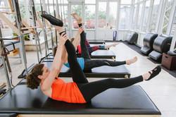 women stretching pilates class