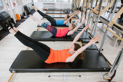 3 women stretching on pilates equipment