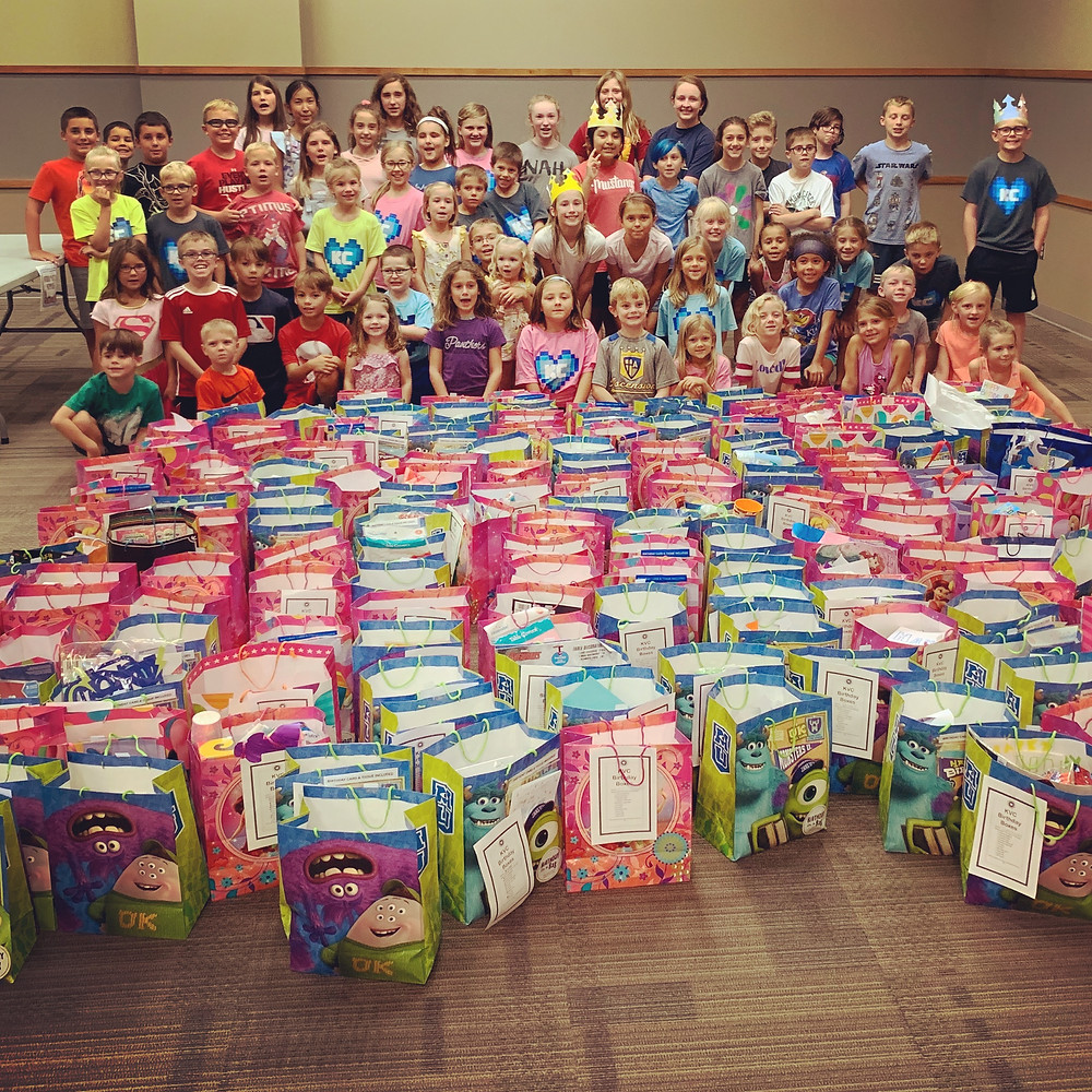 KindCraft kids standing proudly behind their hard work assembling birthday bags for foster children.