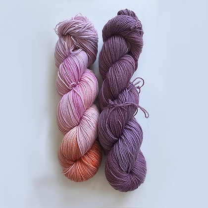 2 skeins of fingering weight yarn, one light pink with splashes of orange & lilac.  The other has various tones of purple