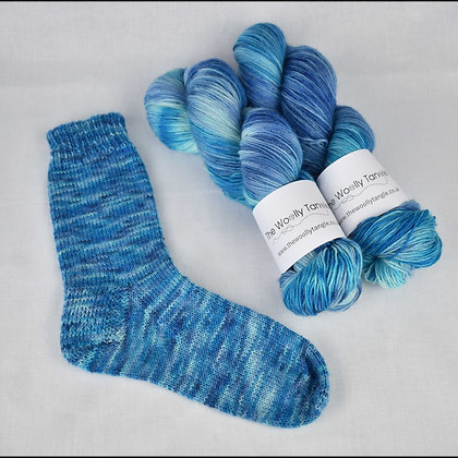 A sample sock with 2 skeins of yarn in Waterways colourway dyed by The Woolly Tangle
