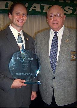 Myron holding Delta College distinguished alumni award standing next to former Sheriff John Reder