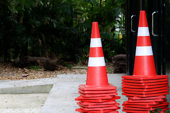 Many traffic cones on cement floor in f