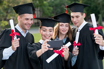 Graduates of college taking a selfie.