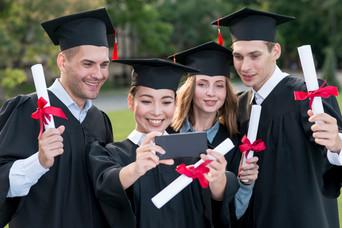 Graduates of college taking a selfie.