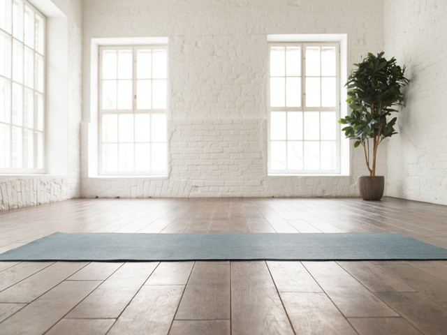 Unrolled yoga mat on wooden floor in mod