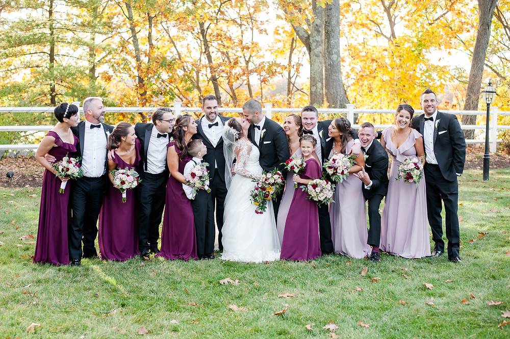 A full wedding party and family members pose while laughing at each other.