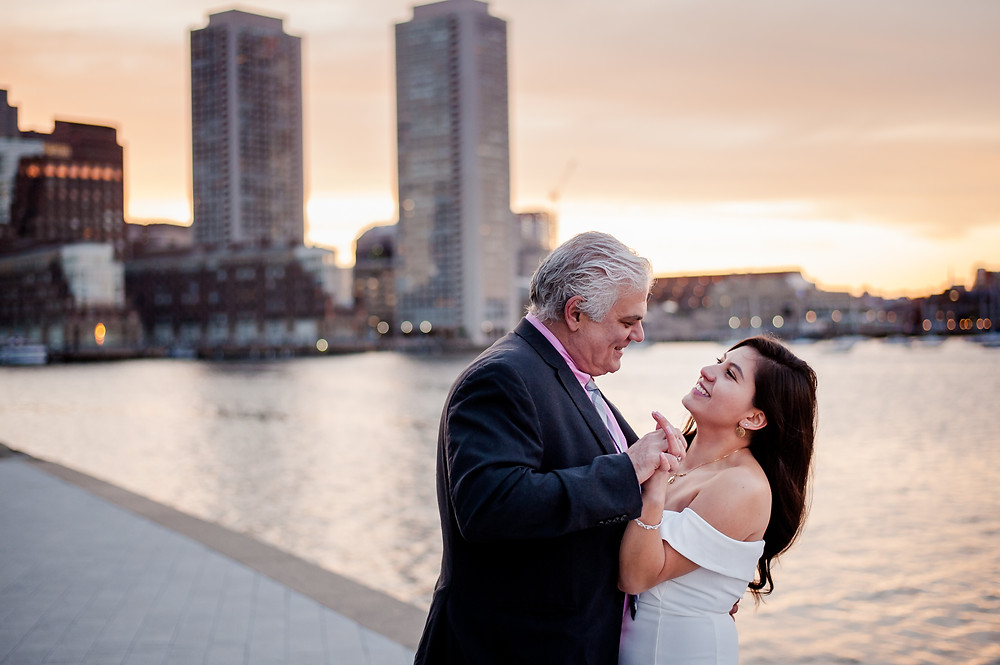 A couple poses by dancing at Fan Pier Park in Boston's Seaport District.  The couple faces each other, with the Boston skyline behind them.