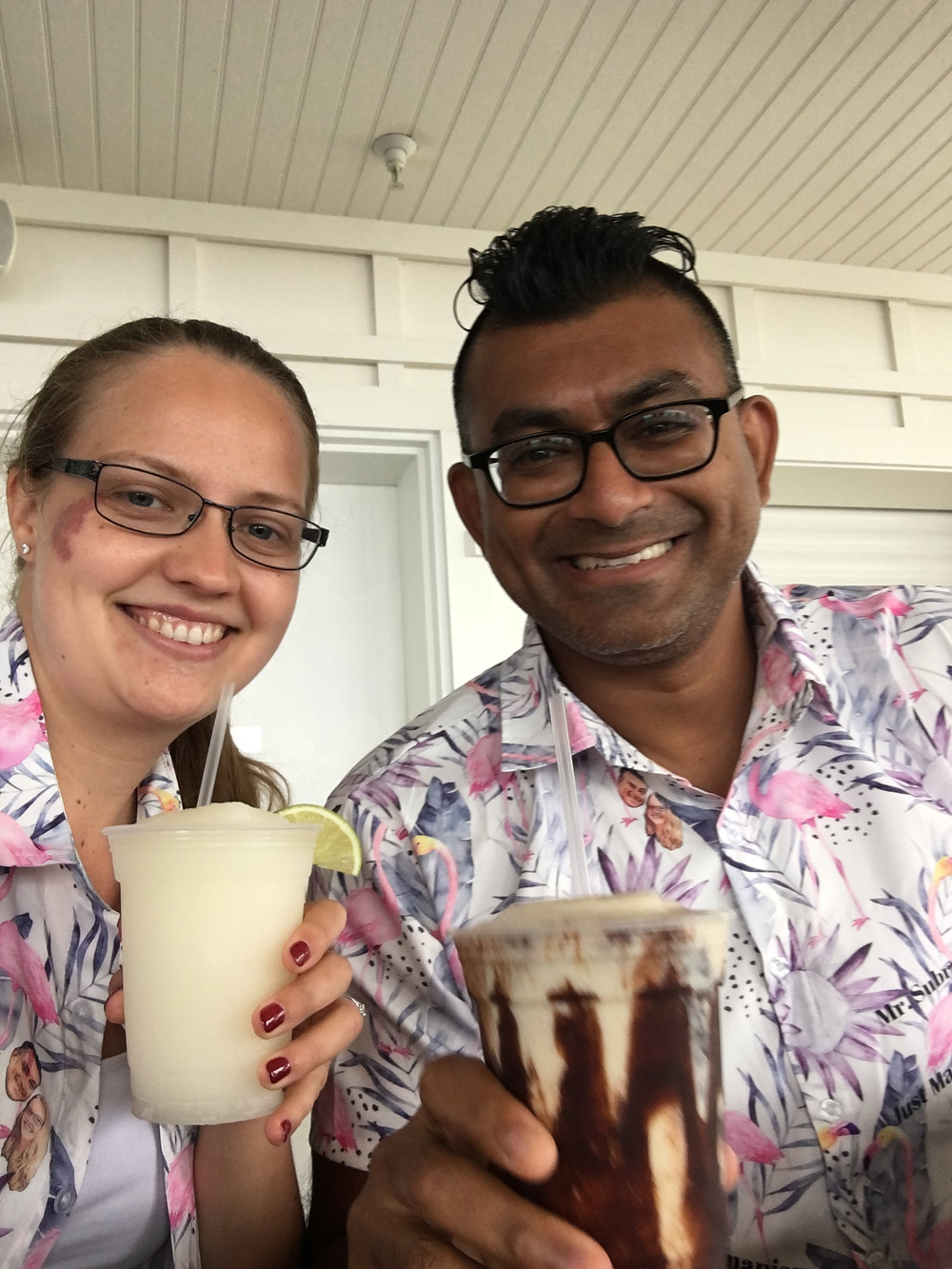 Newlyweds Danielle and Sam toast with frozen drinks at their mini-moon while wearing Sam's favorite Hawaiian shirts, gifted to him by his wife at their wedding.