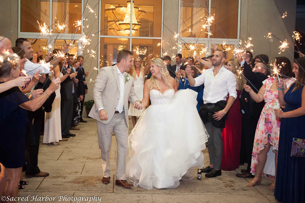Guests hold sparklers above and around the couple, helping them create a memorable end of their ceremony.