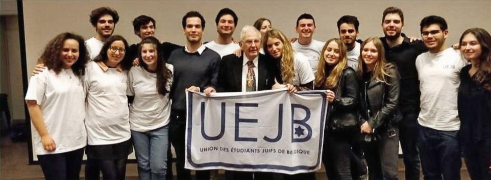 Photo de l'UEJB avec un rescapé de la Shoah tenant un drapeau de l'union.