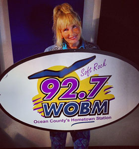 barb-holding-wobm-logo-sign