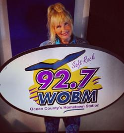 barb-holding-wobm-logo-sign