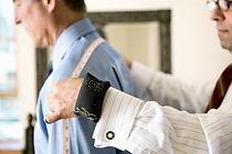 'Rock of Eye' by Anita Sullivan. Tailor measures customer.