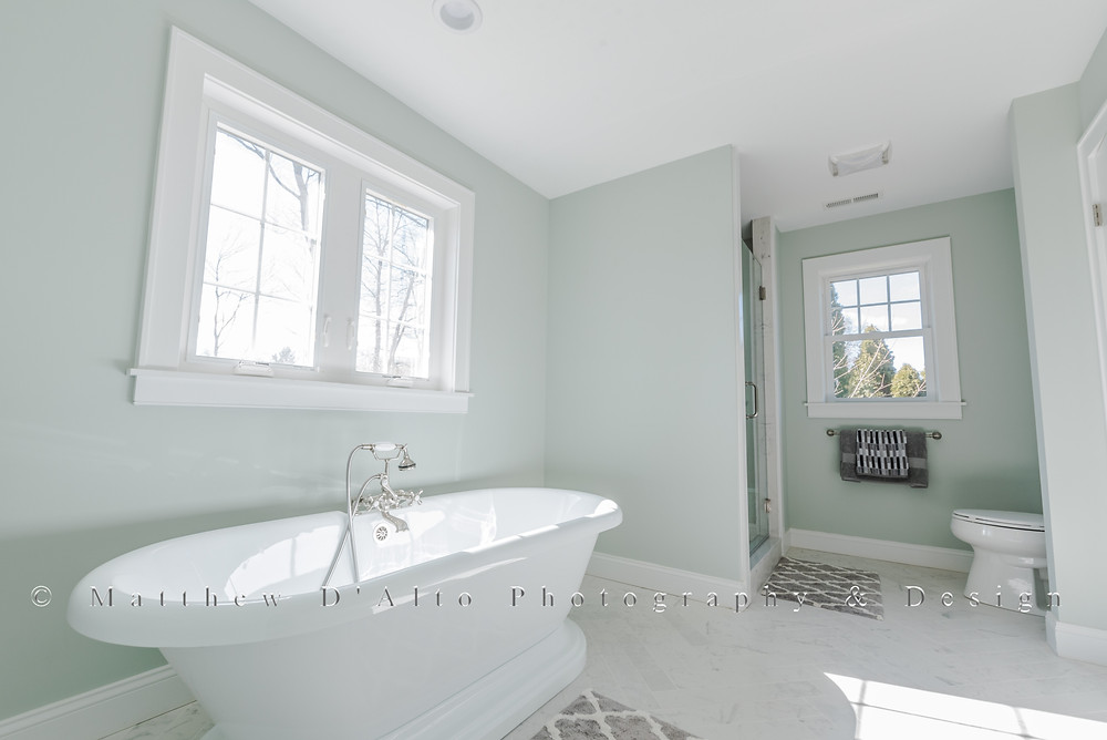 This bathroom photo was produced using a professional camera and lens. Without any adjustments, it shows all of natural distortion of using a wide-angled lens. Walls and edges are slanted and crooked, making the room look less appealing.