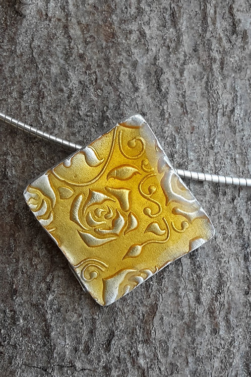 Zilveren reliëfhanger met detail van UV hars.
