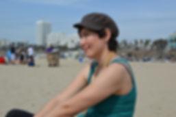 Artist Jaime Lang sitting on beach in Santa Monica