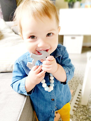 Super cute baby girl chomping on a grey silicone elephant teether attached to a pacifier clip.